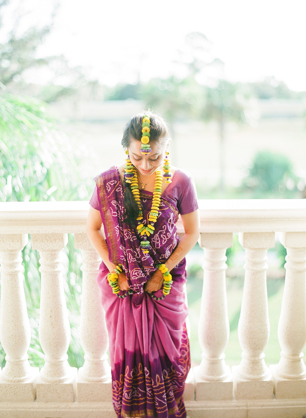 indian bride at her mehndi ceremony wearing a simple purple sari for her mehndi ceremony and yellow floral jewelry and floral tikka headpiece for her indian wedding in palm coast florida at the hammock beach resort photographed by Destination Wedding Photographer Lexia Frank, a top indian wedding photographer who shoots Indian weddings on film and shoots luxury indian weddings in florida and worldwide