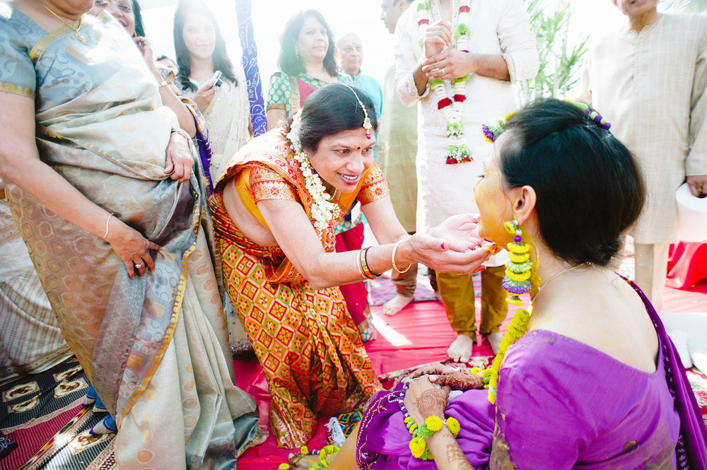 an auntie touches indian bride's face at her pithi ceremony during this hindu wedding in florida while destination wedding photographer Lexia Frank - a top indian wedding photographer , photographs this luxury indian wedding on film because she is a film photographer who shoots indian weddings for brides who love maharani weddings, south asian bride magazine photographers, and manish malhotra