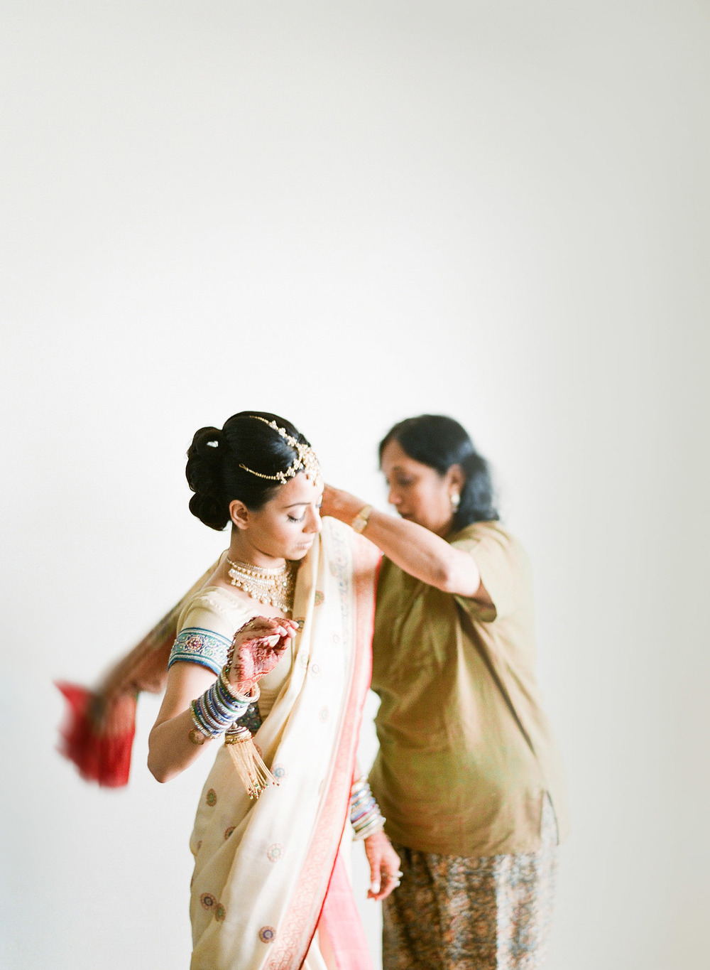 an auntie helps this hindu bride tie her saree for her indian wedding at vizcaya miami While destination wedding photographer, Lexia Frank- ranked top indian wedding photographer , photographs this indian wedding on film because she prefers the beautiful tones and bright colors of film for luxury indian weddings. Lexia photographs indian weddings worldwide. suneet varna and manish malhotra