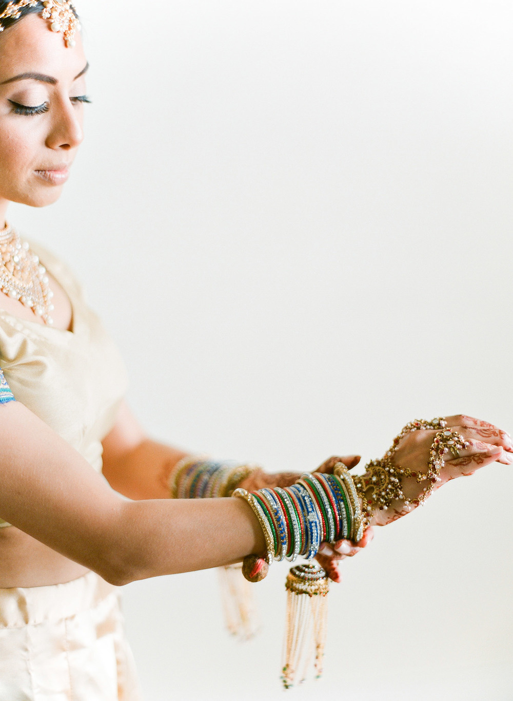this hindu bride adjusts her bangles before her indian wedding ceremony at vizcaya miami where Destination WEdding Photographer Lexia Frank - rated top indian wedding photographer for luxury indian weddings- shoots film for this indian wedding because she prefers the soft skin tones and vibrant colors for indian weddings in india florida, and worldwide. manish malhotra and suneet varna