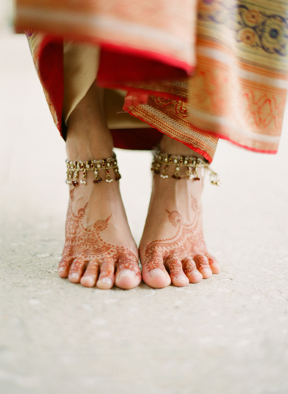 destination wedding photographer lexia frank- a top indian wedding photographer - photographs this luxury indian wedding in florida and the bride's mehndi designs on her feet with anklets  on film as she is a film photographer for indian weddings because she prefers the tonality of film and vibrant colors for indian weddings. manish malhotra