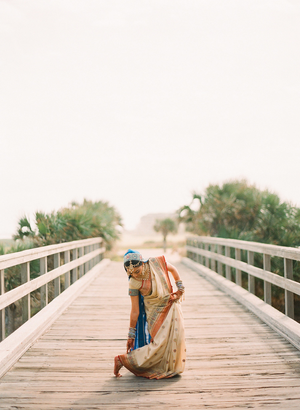 a hindu bride adjusts her saree before her indian wedding in florida photographed by Destination Wedding Photographer, Lexia Frank- a top indian wedding photographer. Lexia Photographs her luxury indian weddings on film preferring the tonal ranges and vibrant colors of film for luxury indian weddings in india, Florida, and worldwide.