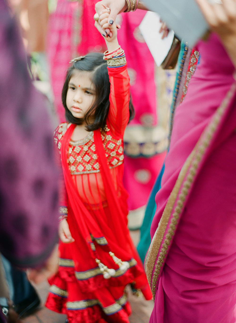 a little girl hold's her mother's hand during the parade at this Indian Wedding in Florida photographed by Destination Wedding Photographer, LExia Frank - a top indian wedding photographer - who shoots film for luxury indian weddings preferring the soft skin tones and vibrant colors for indian weddings in india and worldwide