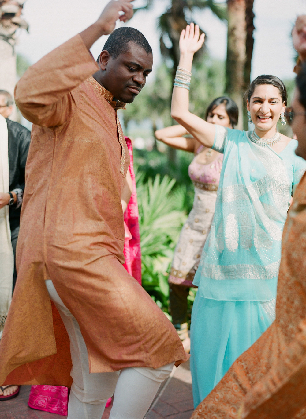 people dance at the groom's parade at this Indian Wedding in Florida photographed by Destination Wedding Photographer, LExia Frank - a top indian wedding photographer - who shoots film for luxury indian weddings preferring the soft skin tones and vibrant colors for indian weddings in india and worldwide