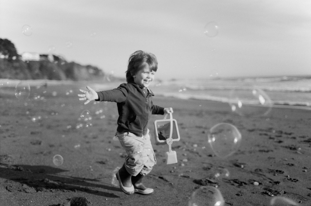 little boy chases bubbles on the oregon coast photographed by Portland Oregon Family Photographer Lexia Frank, a film photographer in portland oregon