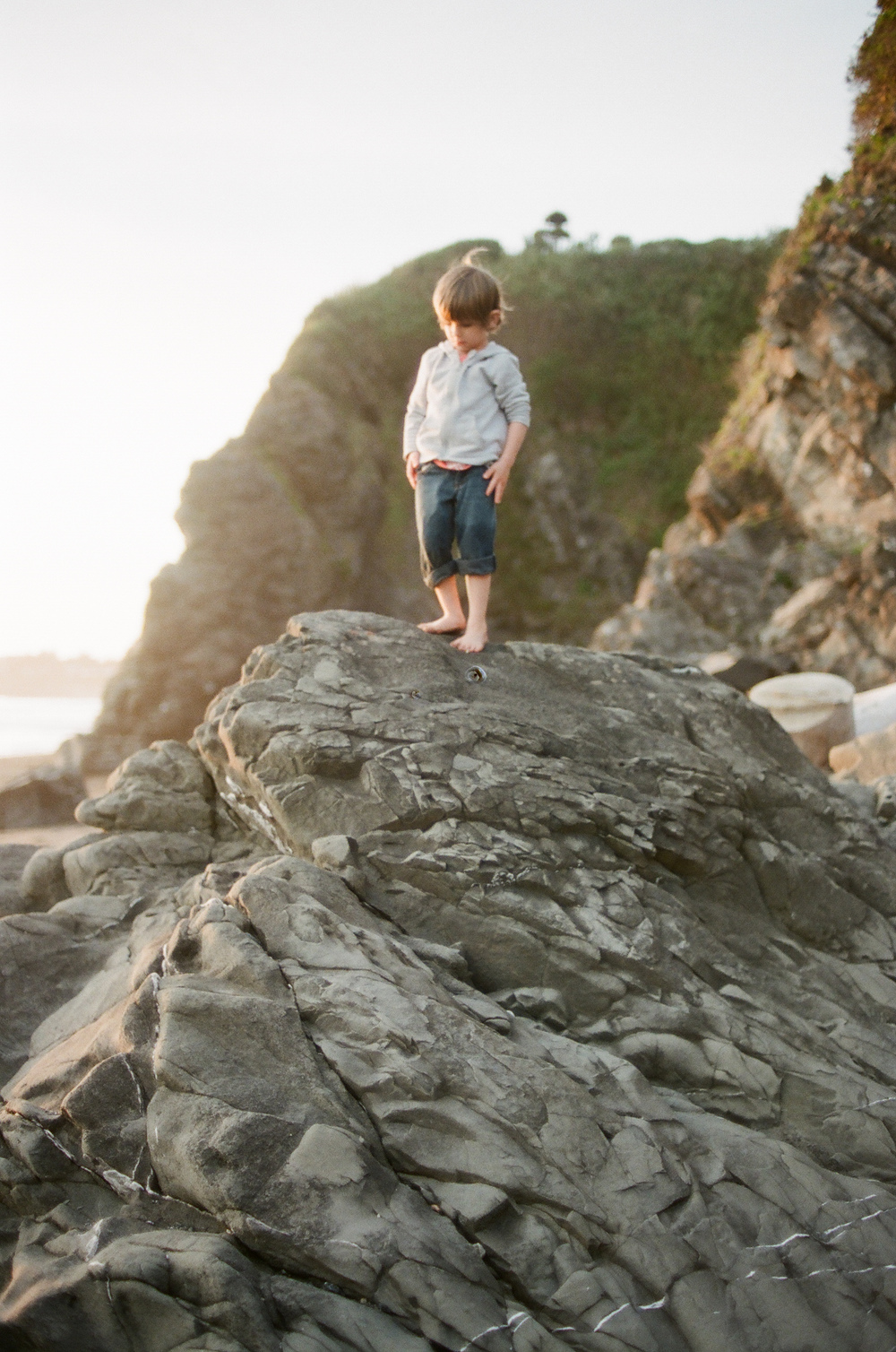 A boy stands on a rock in Seaside Oregon, while Portland Oregon Family Photographer- Lexia Frank - photographs this family on film. she does lifestyle family sessions in portland oregon and the oregon coast