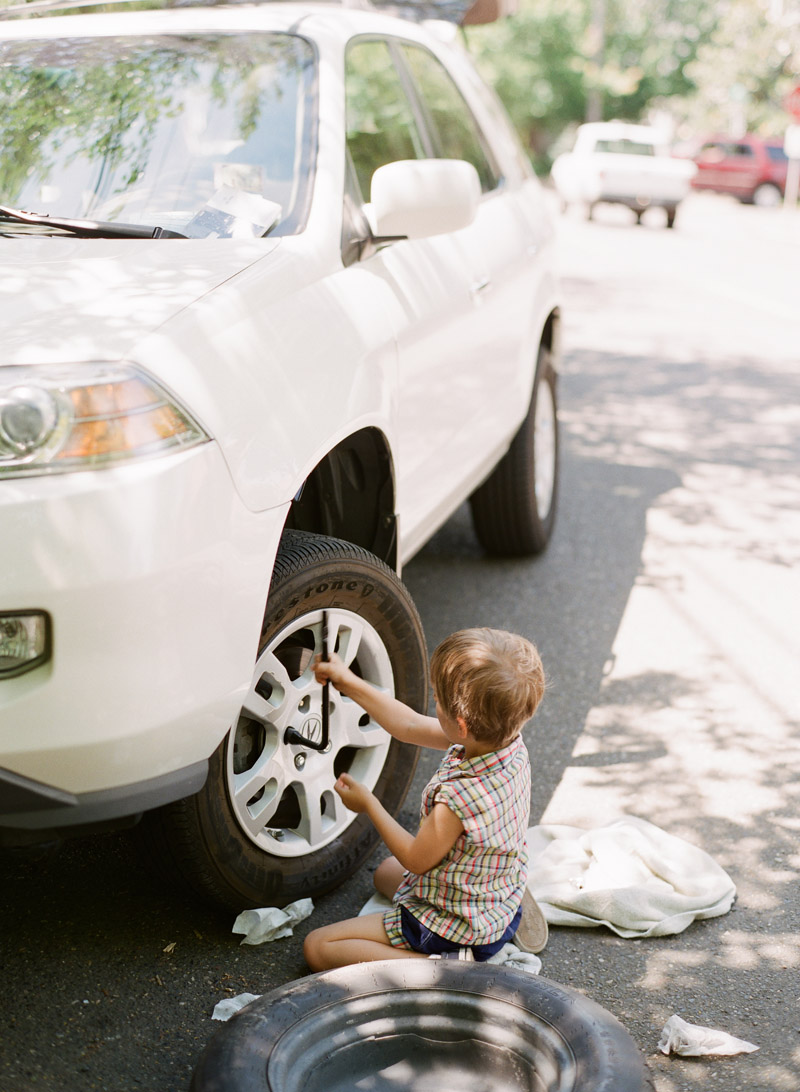 a little boy changes a tire in portland oregon during this Lifestyle Family Session with Portland Oregon Lifestyle Family Photographer - Lexia Frank - a film photographer in portland oregon