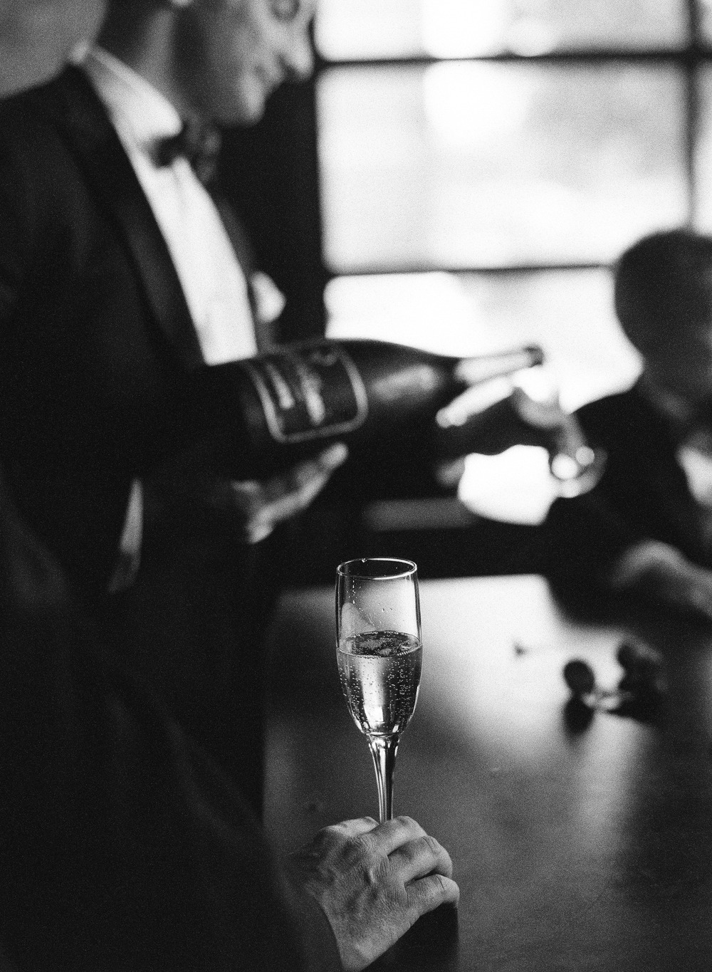 Destination Wedding Photographer Lexia Frank is a film photographer on the west coast specializing in luxury weddings and fine art film photography. In this article she writes a letter to the groom, and talks about the groom's role in photography. a groom pours a glass a champagne at the Iron Horse Inn in Milwaukee Wisconsin before his wedding at the Villa Terrace Milwaukee Wisconsin.  www.lexiafrank.com