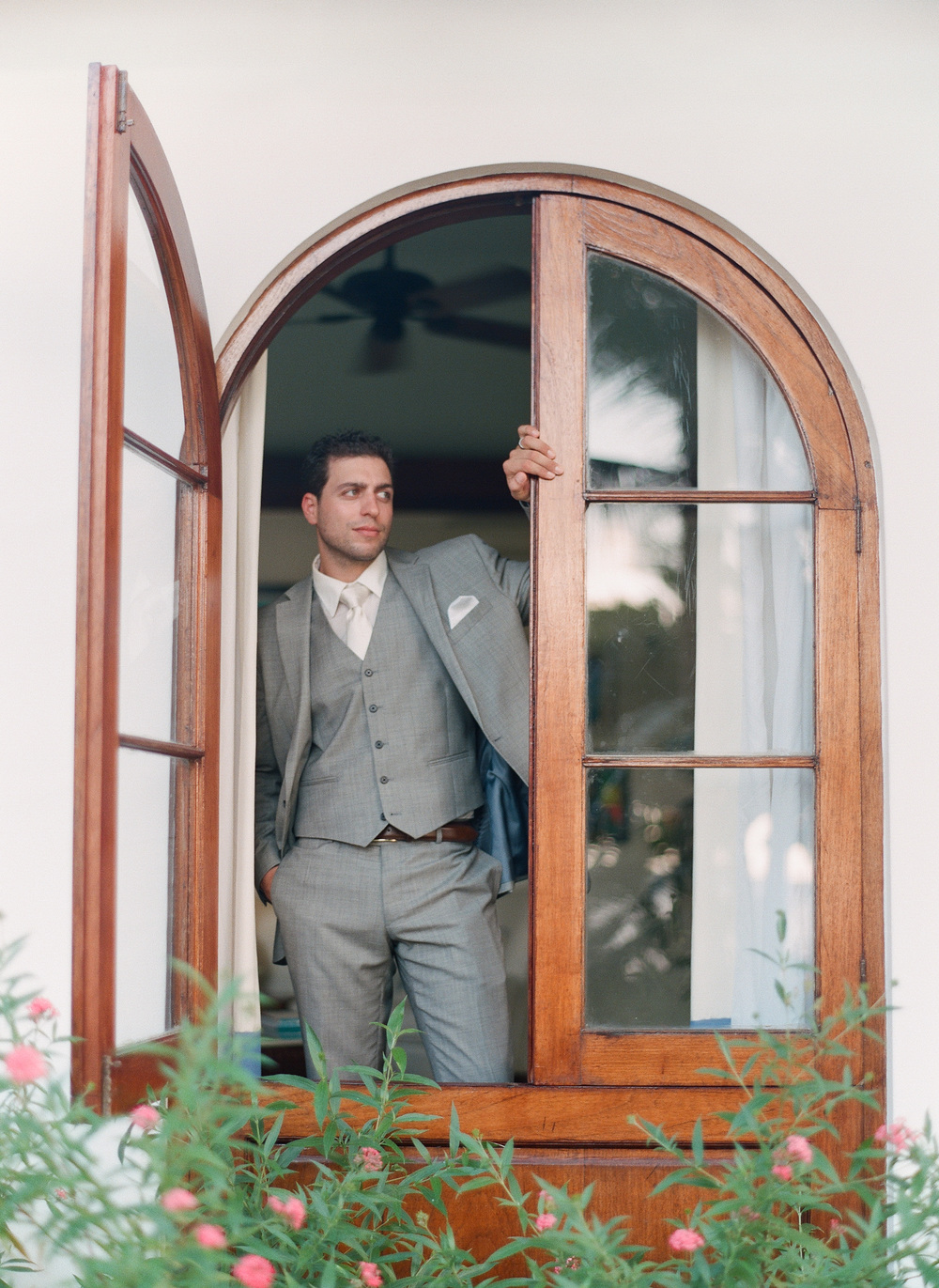 Destination Wedding Photographer Lexia Frank is a film photographer on the west coast specializing in luxury weddings and fine art film photography. In this article she writes a letter to the groom, and talks about the groom's role in photography. Groom poses in a casement window at Roundhill Jamaica before his Roundhill Jamaica wedding  www.lexiafrank.com