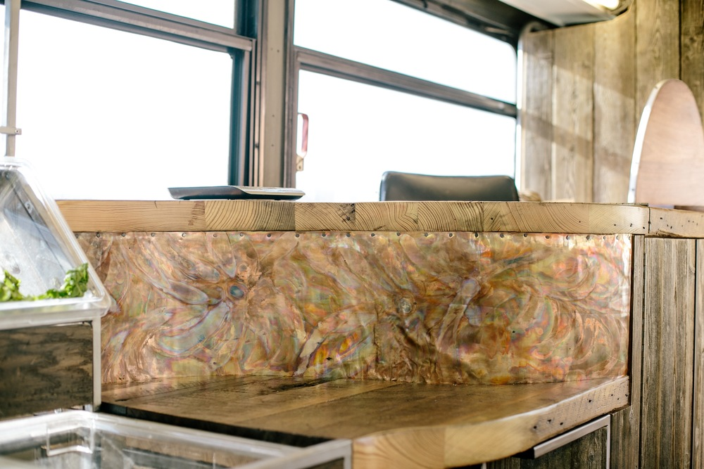 A Torch Painted Copper Mural, Fastened With Copper Nails Brings A Rustic Blend Of Color And Texture To The Face Of The Checkout Counter.