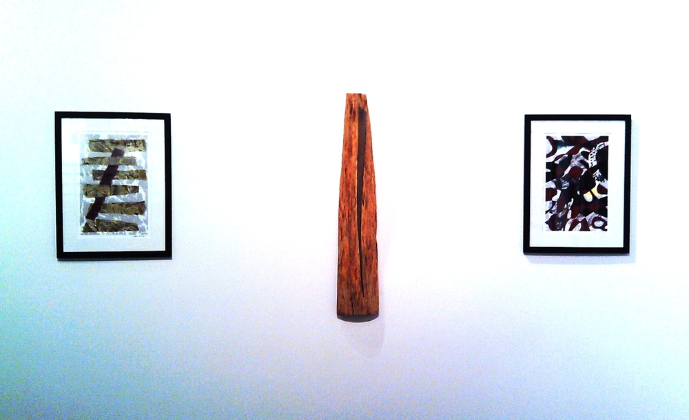 Sculpture flanked by two monoprints
