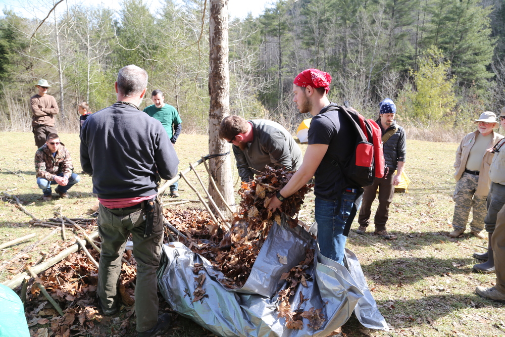 Course participants pile on leaves during the construction of a debris hut. Photo by Todd Nystrom.
