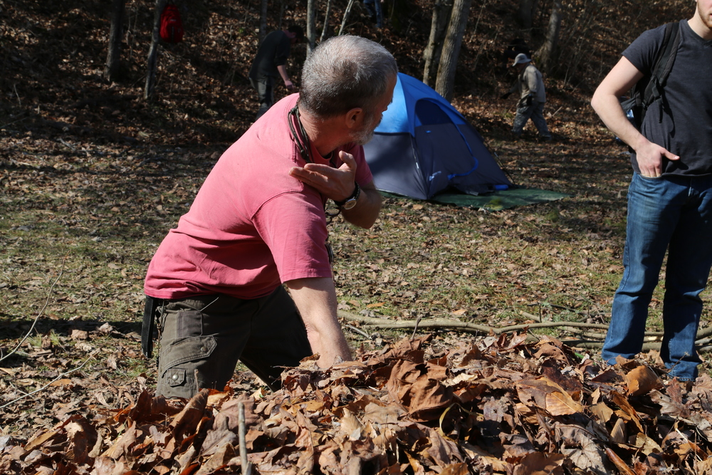 As John demonstrates in this photo, the debris hut shelter requires a significant depth of leaves in order to provide adequate insulation and rainproof qualities. Photo by Todd Nystrom