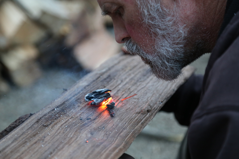 "John demonstrates ""coal burning,"" a technique for making bowls, spoons, and other implements that make survival easier, as well as passing time around the campfire. Photo by Todd Nystrom."
