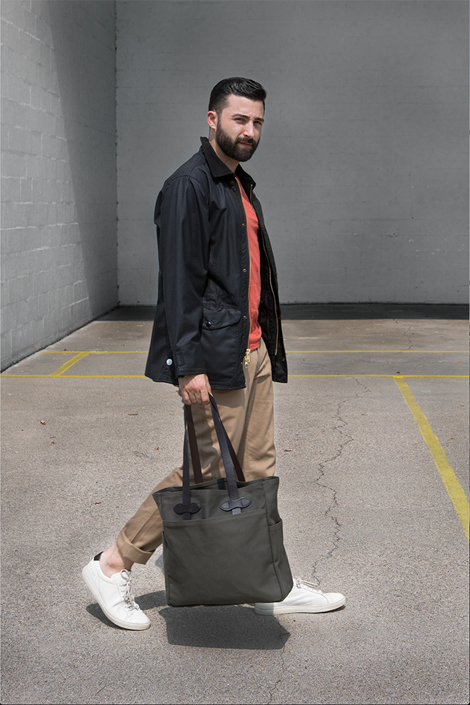 Jordan is wearing a black Cover Cloth coat and twill otter green tote by Filson, Save Khaki burnt orange tee shirt and the Oliver pant by Steven Alan.