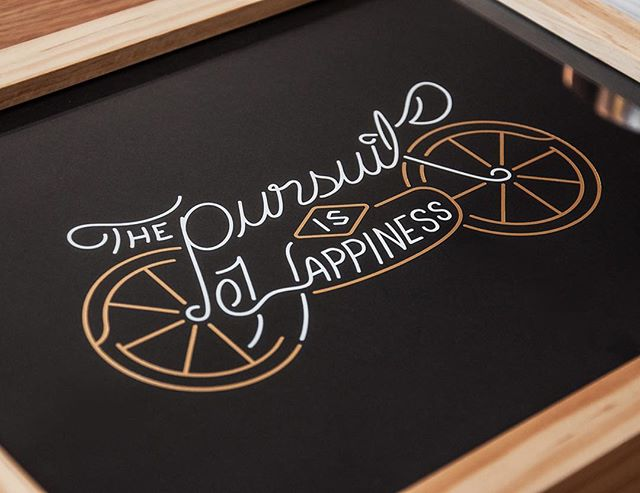 Gold & white letterpressed foil details on our Pursuit is Happiness print by @brianwooden + @seanametcalf.  Order by Wednesday morning for guaranteed shipment for Christmas. This is a limited edition print, so once they're gone, they're gone! (Link in profile). #youngandunited #design #thedesigntip #goodtype #typography #lettering #illustration