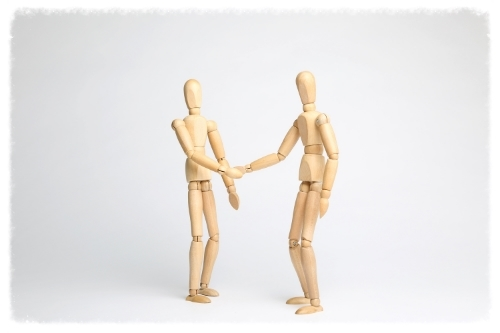 Wooden mannequins shaking hands