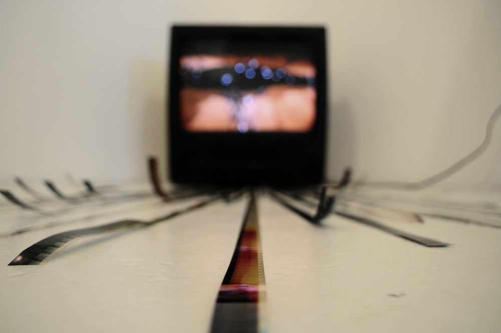 'Möbius' Video installation / TV, 16mm film strips, black acrylic paint.