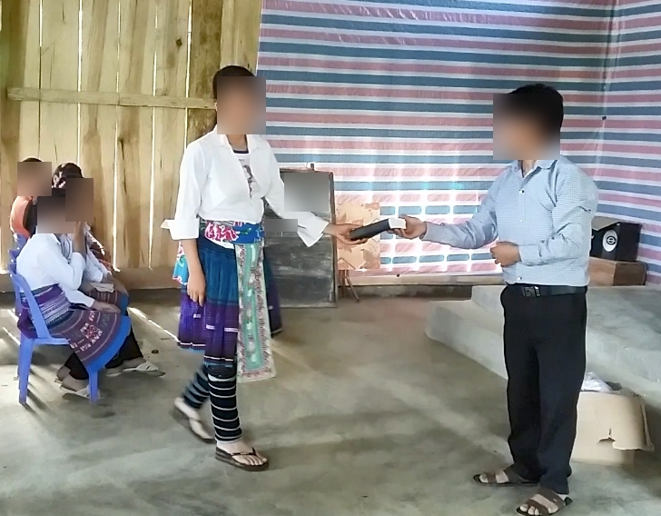 Photo: Black Hmong woman receives her first Bible.