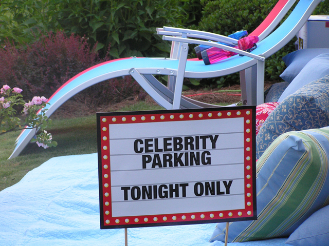 Set up a special VIP seating area for the guest of honor with quilts, pillows, or chaise lounges. The sign is from Oriental Trading.