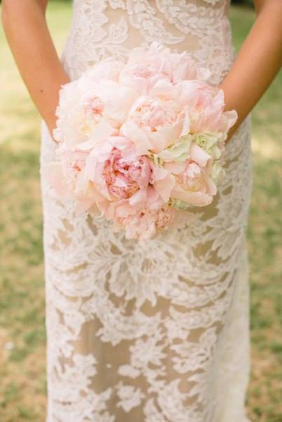 Massive bouquets of one type of flower make an impressive statement. These blush peonies are so fragile against the bride's gown, a perfect compliment. Photo: Arden Photography