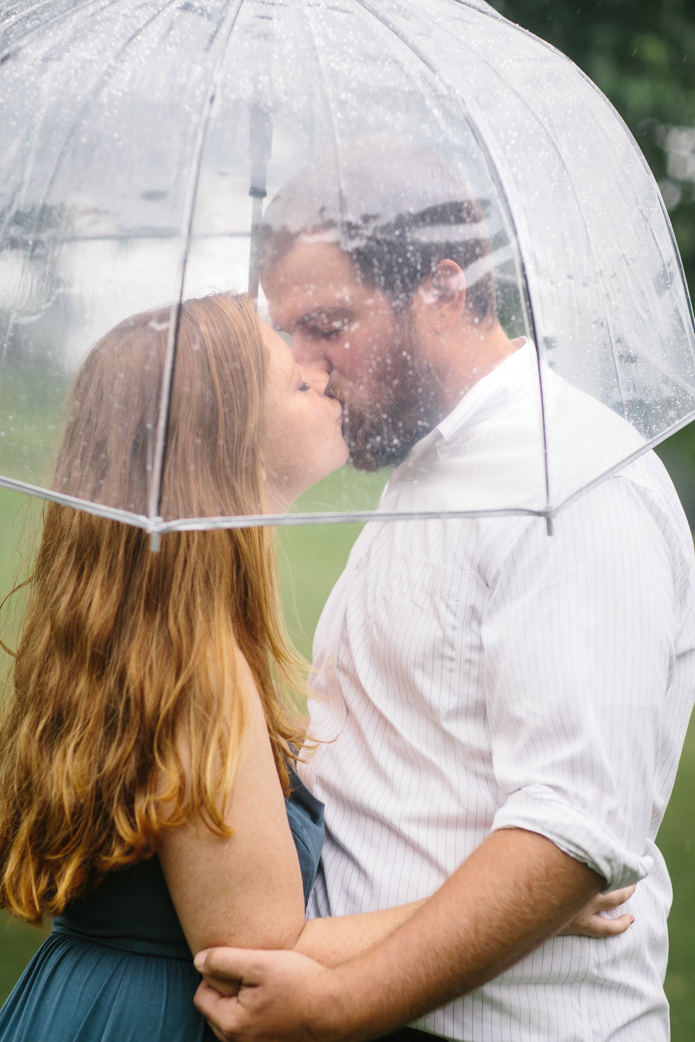 kiss under umbrella.kissing in the rain.rainy engagement photos.engagement photo inspiration.clear umbrella.JPG