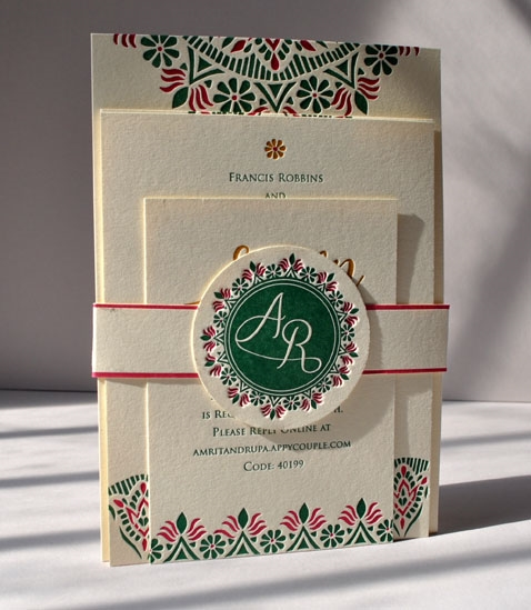 Rangoli wedding invitation suite with a monogrammed belly band. Printed on Crane's Lettra Ecru in 3 colors with a belly band.