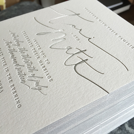 Modern calligraphy foil stamped in silver for letterpress wedding invitation with edge painting