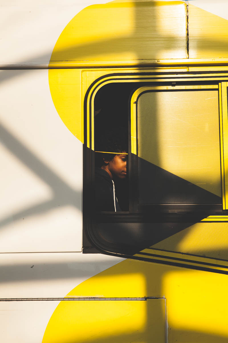 A young boy sits on the bus outside of the Metro
