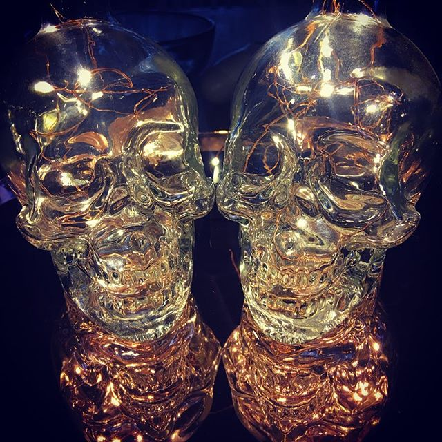 A cool way to repurpose your @crystalheadvodka empties. Using led string lights on copper wire and a rose gold tray from @kmartaus #upcycledtreasures #easiestdiyever #diy #dayofthedead #skulls #gothichomedecor #lights #myaesthetic #waytojazzupatraylol #drinkvodka #tablecenterpiece