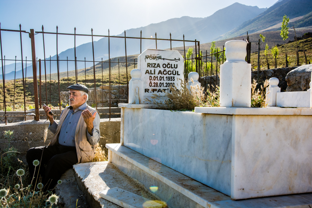 A dede recites poem-prayers beside the grave of a man from his village.