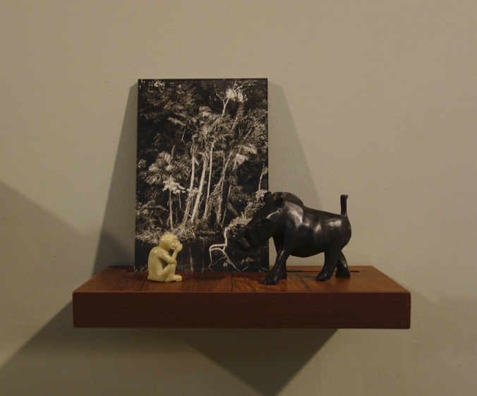 Donna ONG  Postcards from the Tropics (v)  2016 Diasec print, wooden shelf, and tropical souvenirs (wooden boar and stone monkey) Dimensions variable
