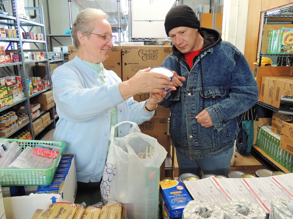 Sister Dorothy Miller, RSM reviews with an Intersection guest the nutrition label on one of the canned goods he received in his grocery 'dry bag.' (Photo © 2018 by Micaela Young for Pittsburgh Mercy and The Intersection. Used with permission.)