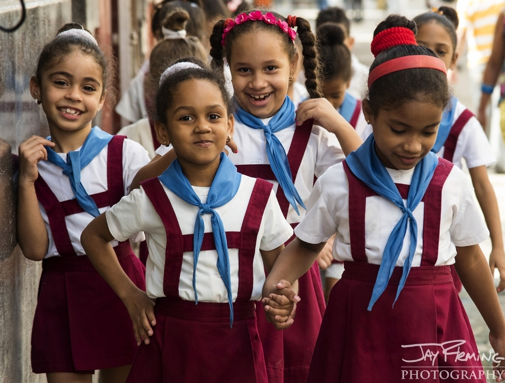 Cuban schools are entirely run by the government. Attendance in school is mandatory unitl age 15 and uniforms are required. These outfits indicate that the girls are in primary school.