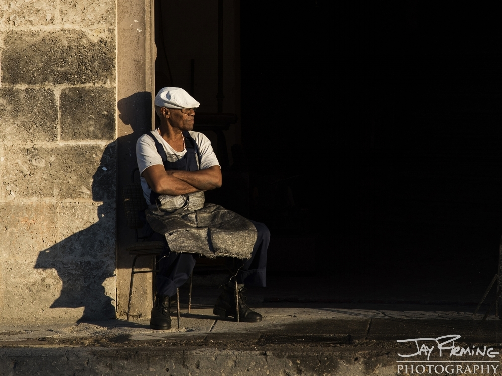 A man working at a shoe repair shop takes in the morning light on calle Neptuno