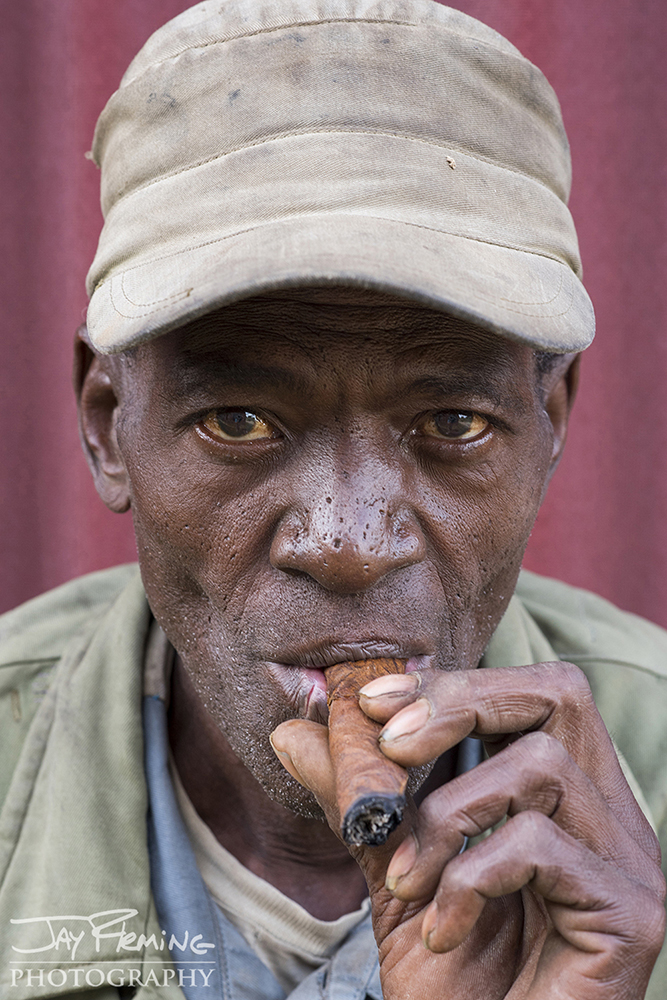 Laborer at the Gonzalez tobacco plantation takes a break from hanging tobacco for a cigar. Pinar del Rio