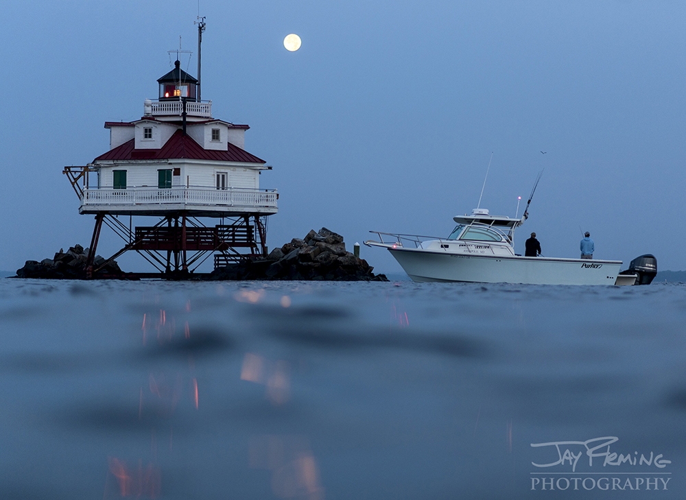 Fishermen targeting Striped Bass at Thomas Point Shoal Light as the moon sets in the west.