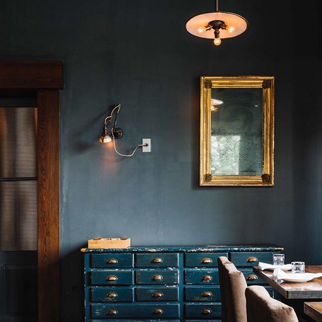 A vignette from one of our favorite, past restaurant projects, Empire State South in Atlanta. ESS is the baby of James Beard Award winning chef Hugh Acheson.  All of the lighting was designed and fabricated Robert Odgen  using vintage, salvaged materials. The walls were painted in one of our favorite finishes - Milk Paint, which is eco-friendly and gives the perfect textured, matte finish. Photo by Andrew Thomas Lee. Antiques through Hawthorne House.  We designed Empire State South in 2010 with Susan Hable.  Hable fabric throughout. ⠀⠀⠀⠀⠀⠀⠀⠀⠀ @essouth @hughacheson @andrewthomaslee @lostineathome @beardfoundation #restaurantdesign #restaurantinterior #foodie #jamesbeardchef #esquiremag #huffposttaste #atlantarestaurants #bonappetit #buzzfeedfood #lisaellisdesign #athensgeorgia #interiordesign #designdetails  #bestoftheday #milkpaint #customlighting