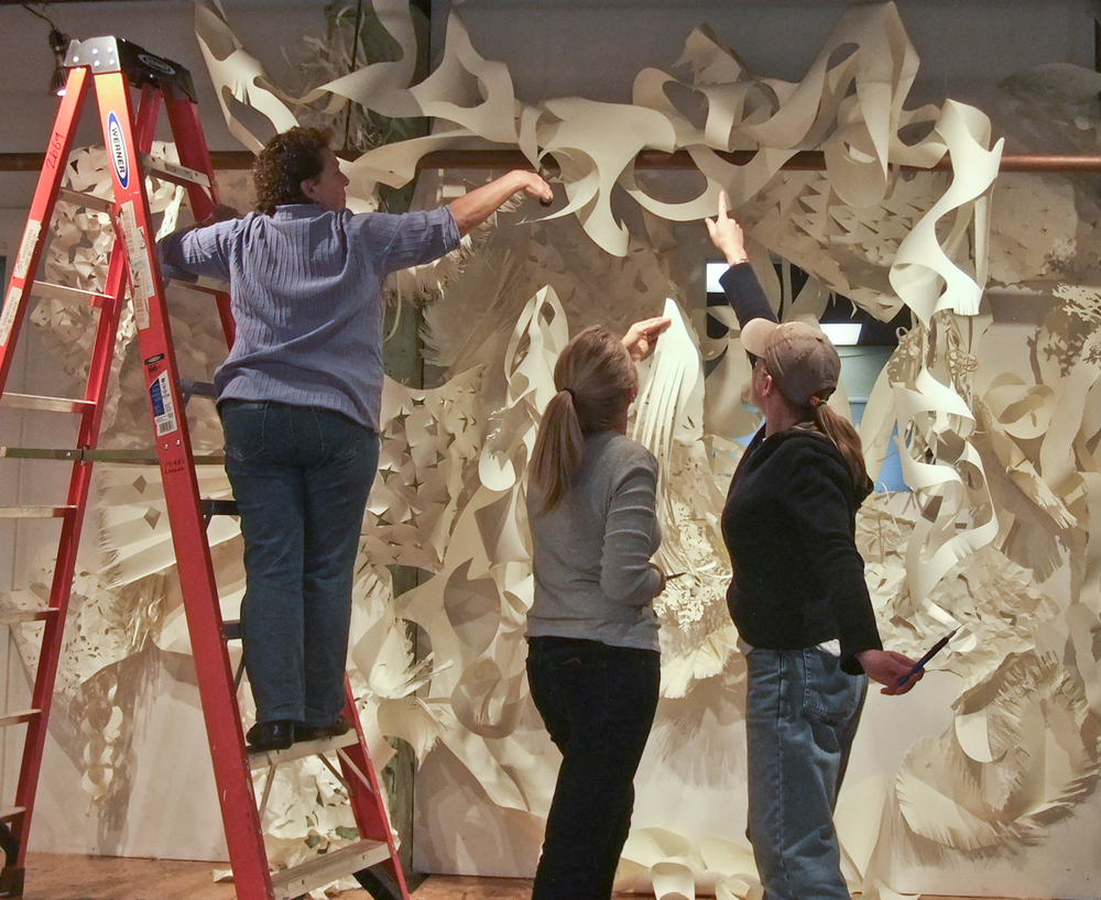 Kay Hartung, Carrie Childs Antonini and Cheryl Clinton work together to complete 'Cut/Fold/Tear' installation.