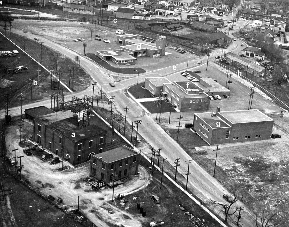 Aerial photo of Greenwich St, 1955.  Image courtesy of the Brant Historical Society   a) Brantford Hydro substation, b) CNR connecting track to the Toronto, Hamilton & Buffalo Railway (TH&B), c) CNR rail line to Tillsonburg, d) Fire Station, e) Newport Street, f) Police Station, g) Masonic Temple. Brantford Mosque since 2005, h) Former Brantford Hamilton Electric Radial Railway line, i) Clarence Street.