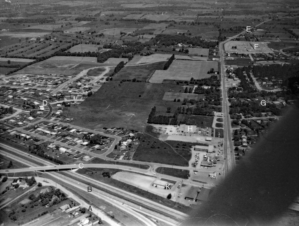 Aerial photo, Mayfair Gardens  Image courtesy of the Brant Historical Society   A) Barnes Avenue, B) Highway 403, C) Tollgate Road, D) Mayfair Gardens subdivision, E) Highway 24, F) Brantford Plaza, Woolco, G) Dunsdon Street, city limits, King George Road reduces to two lanes as it enters Brantford Township, H) Dingwall Motors, Mercury-Lincoln dealer, I) Farmers' Dell Plaza, J) Dairy Queen, K) Dunsdon Legion Branch 461.
