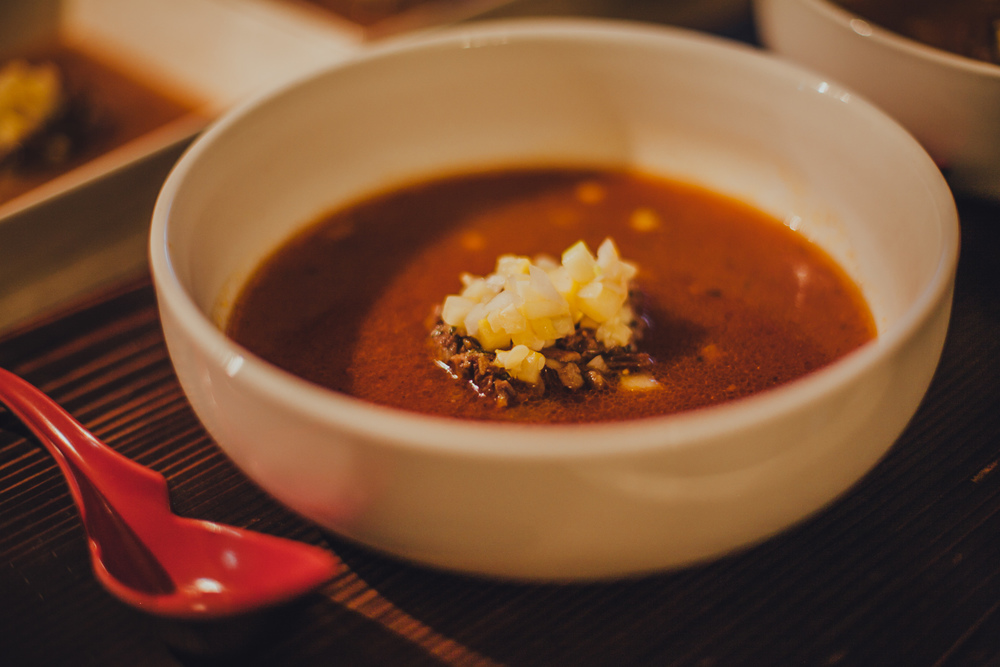 Tomato-based oxtail soup, served with diced squash, onions and zucchini.