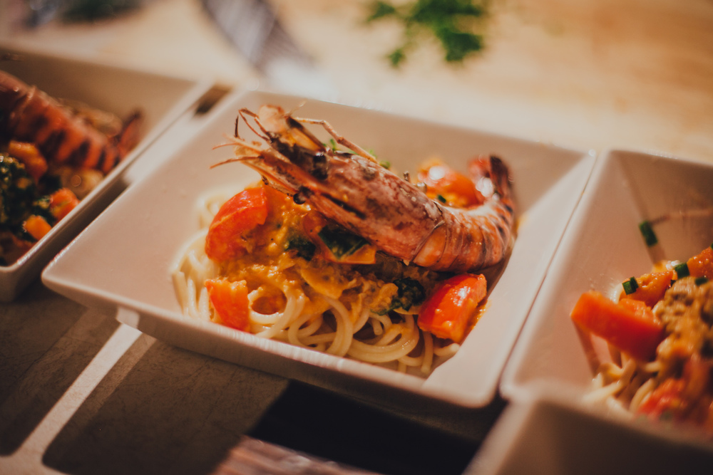 Pasta tossed in a seafood-based sauce, served with tomatoes, clams and grilled prawns.