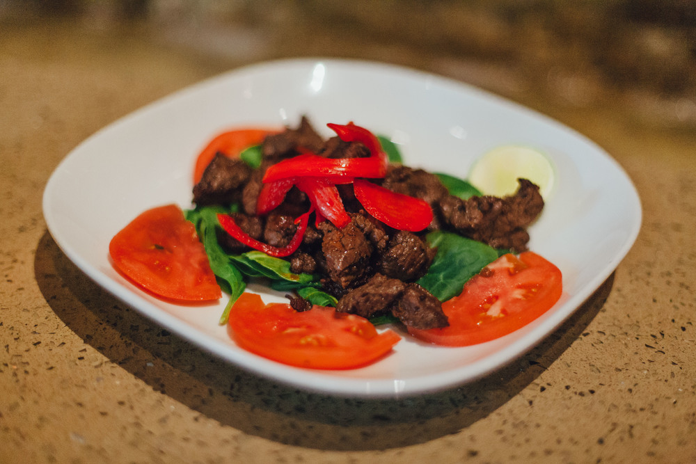 Luc Lac Beef Tenderloin: Marinated tender beef served atop a bed of spinach and tomatoes, accompanied with Rock 'N Raw's house-pickled jalapeno and habanero peppers.