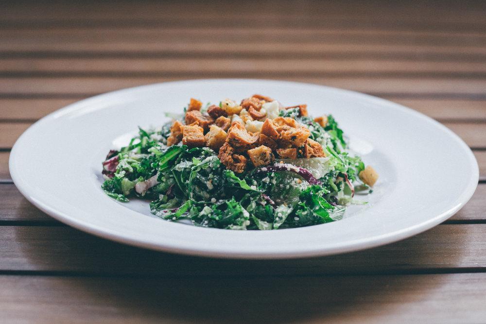 Caesar Chop Salad:Crisp Romaine, Shredded Baker Farm Kale, Radicchio, Chopped Egg, Parmesan, Caesar Dressing and Ciabatta Parmesan Croutons