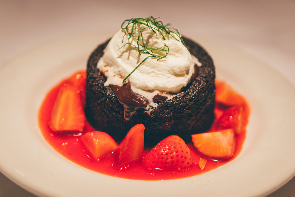 Chocolate Lava Cake: Rich chocolate cake with molten center, served warm, topped with fresh strawberries and house-made whipped cream