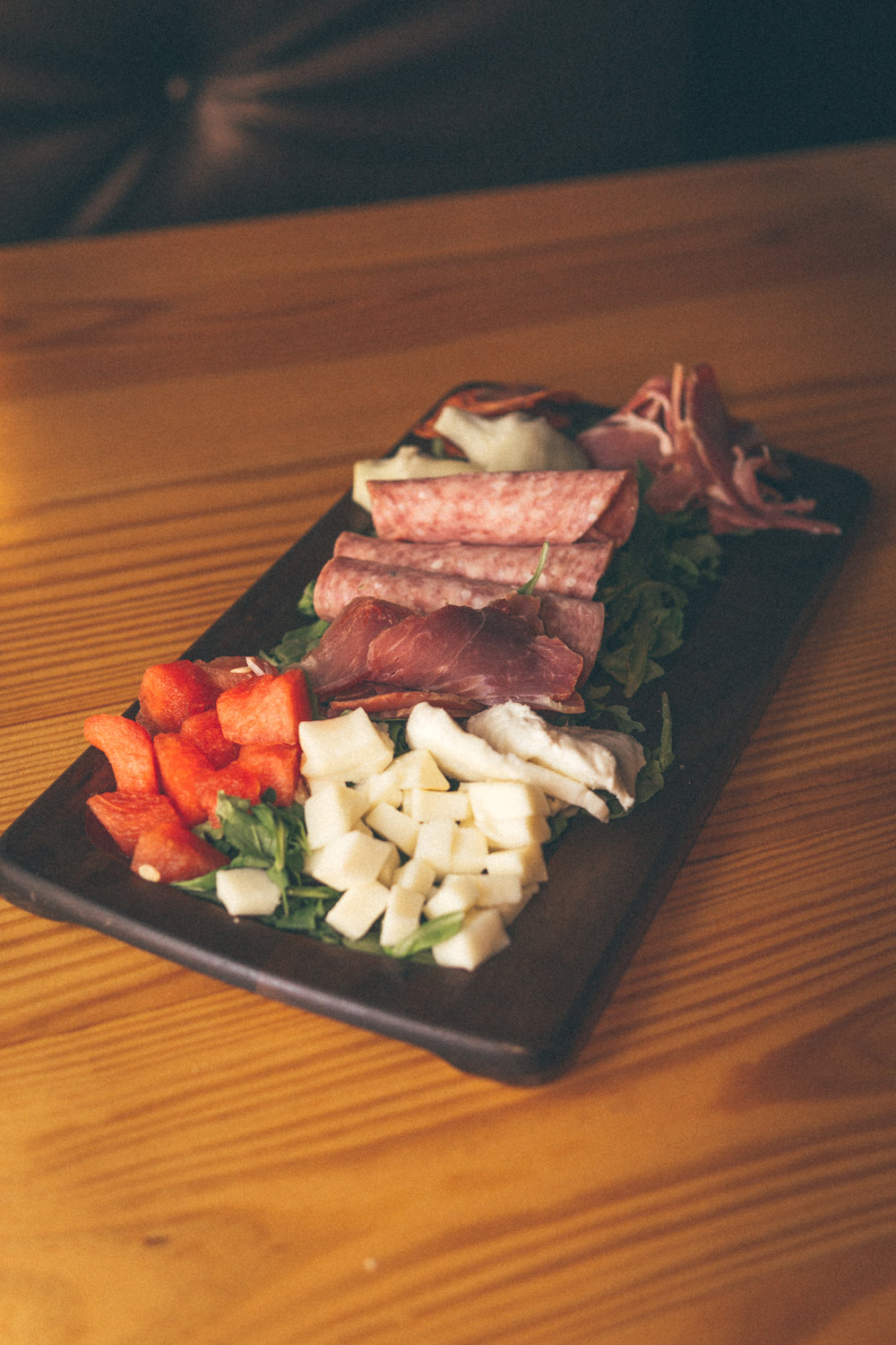 Meat + Cheese Board: Provolone and fresh mozzarella, salami, capicola and pepperoni, and artichokes and watermelon chunks atop a bed of arugula. Offering varies daily.