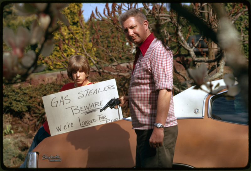 """Country's fuel shortage led to problems for motorists in finding case as well as paying much more for it, and resulted in theft from cars left unprotected. This father and son, made a sign warning thieves of the possible consequences."" David Falconer, Portland, Oregon, April 1974 (412-DA-13063)"