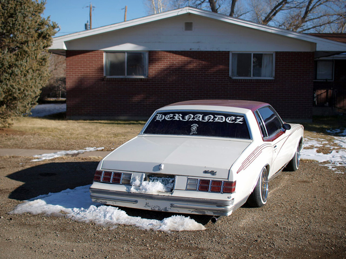 A lowrider in front of a brick house