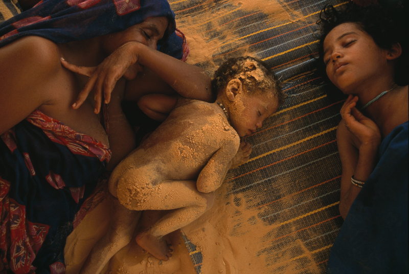 Joanna B. Pinneo, Sub-Saharan Mali, 1997 Blowing sand from a dry lake bed clings to Tinalbaraka walet Mohamed's eight-month old daughter, Isah, as mother and children sleep on a sun baked afternoon in Mali.